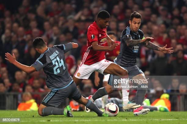 Facundo Roncaglia and Hugo Mallo of Celta Vigo challenge Marcus Rashford of Manchester United during the UEFA Europa League semi final second leg...