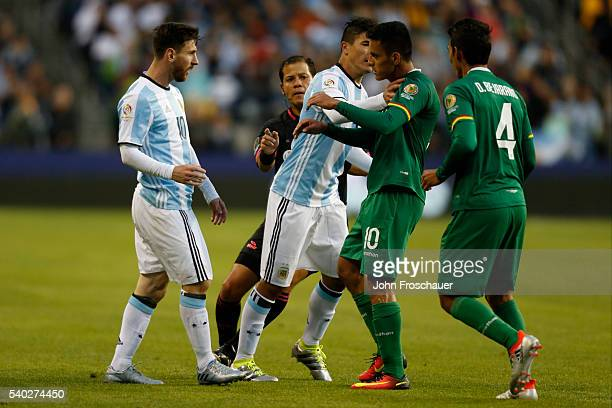 Facundo Roncaglia of Argentina stands between Lionel Messi of Argentina and Jhasmani Campos of Bolivia during a group D match between Argentina and...