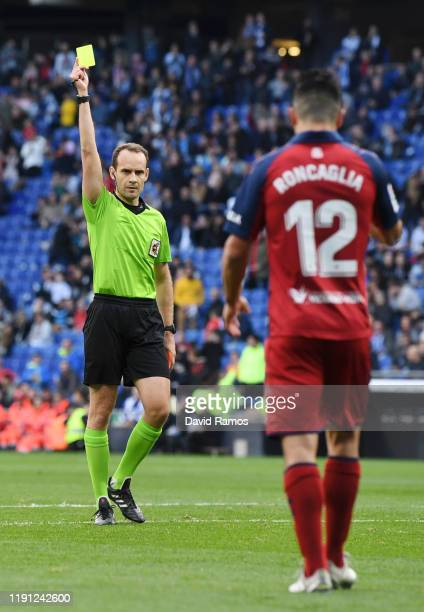 Facundo Roncaglia of Osasuna is shown a yellow card by referee Mario Lopez during the La Liga match between RCD Espanyol and CA Osasuna at RCDE...