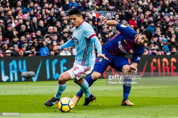 Facundo Roncaglia of RC Celta de Vigo competes for the ball with Luis Suarez of FC Barcelona during the La Liga 201718 match between FC Barcelona and...