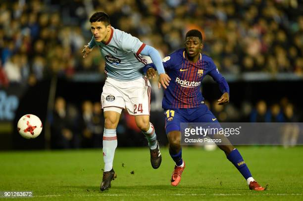 Facundo Roncaglia of RC Celta de Vigo competes for the ball with Ousmane Dembele of FC Barcelona during the Copa del Rey round of 16 first leg match...