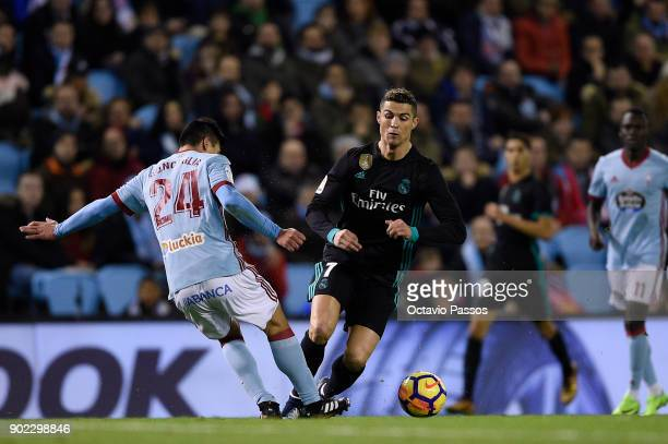Facundo Roncaglia of RC Celta de Vigo competes for the ball with Cristiano Ronaldo of Real Madrid during the La Liga match between RC Celta de Vigo...
