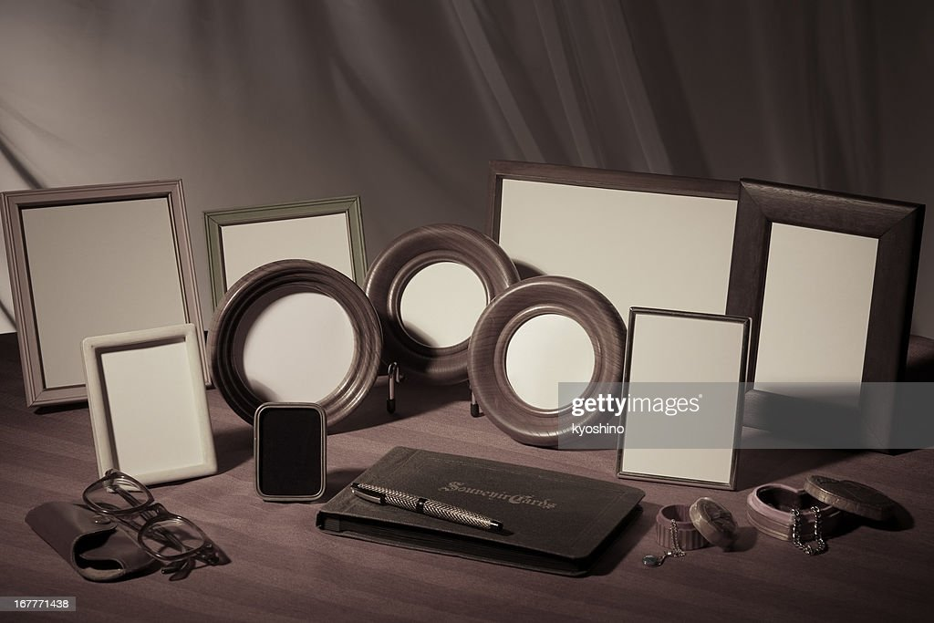 Faded image of blank picture frame on wooden table : Stock Photo