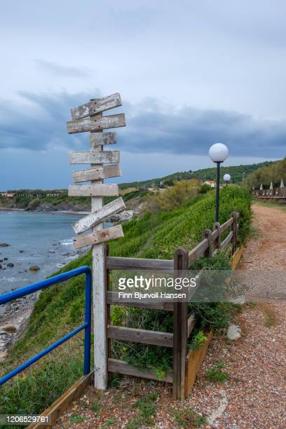 faded pole with wooden signs on a promenade in livorno - finn bjurvoll stock pictures, royalty-free photos & images