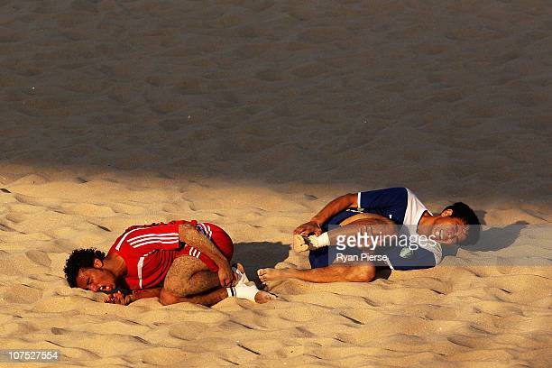 Fadhl Naseer of Yemen and Arslon Sharapov of Uzbekistan lay on the sand after a heavy clash during the Beach Soccer match between Yemen and...