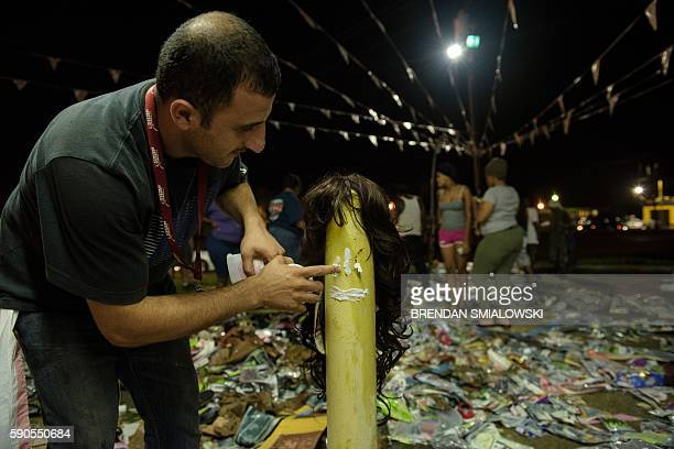 Fadi Omar dresses a pole as a mannequin as people sort through water damaged items outside Jasmine's Beauty Supply following the floods on August 16,...