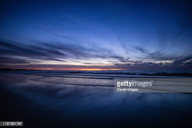 fading sunset on a wet sand beach - fading stock pictures, royalty-free photos & images