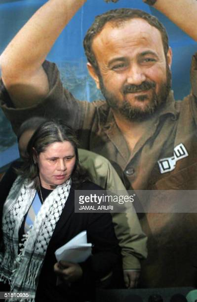 Fadwa Barghuti the wife of jailed West Bank Fatah leader Marwan Barghuti walks past a portrait of her husband after she presented Marwan's candidacy...
