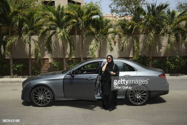 Fadya Fahad one of the first female drivers for Careem, a peer-to-peer ride sharing company similar to Uber, speaks on a mobile phone next to a car...