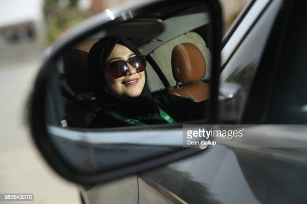 Fadya Fahad one of the first female drivers for Careem a peertopeer ride sharing company similar to Uber is seen in the driver's side mirror of a car...