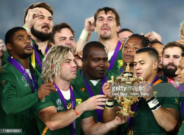 Faf de Klerk and Cheslin Kolbe of South Africa celebrate with the Web Ellis cup following their team's victory against England in the Rugby World Cup...