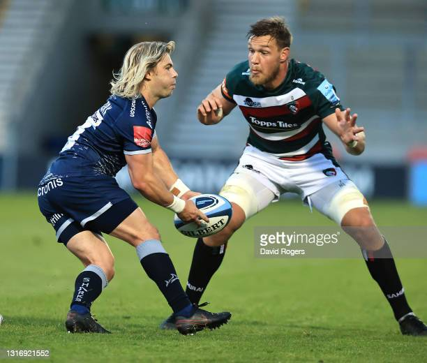 Faf de Klerk of Sale Sharks passes the ball watched by Handro Liebenberg during the Gallagher Premiership Rugby match between Sale Sharks and...