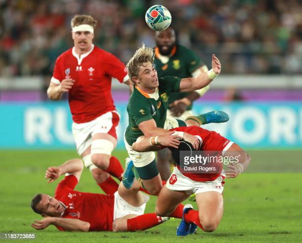 Faf de Klerk of South Africa battles for possession with Leigh Halfpenny and Gareth Davies of Wales during the Rugby World Cup 2019 SemiFinal match...