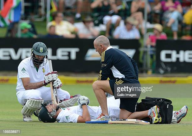 AFRICA JANUARY 12 Faf du Plessis of South Africa gets treatment after being struck in the groin with Hashim Amla looking on during day 2 of the 2nd...