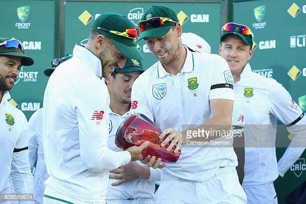Faf du Plessis of South Africa hands the trophy to Kyle Abbott of South Africa after winning the series 21 during day four of the Third Test match...