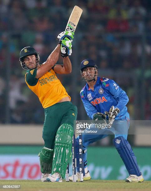 Faf du Plessis of South Africa hits a boundary as MS Dhoni of India looks on during the ICC World Twenty20 Bangladesh 2014 2nd SemiFinal match...