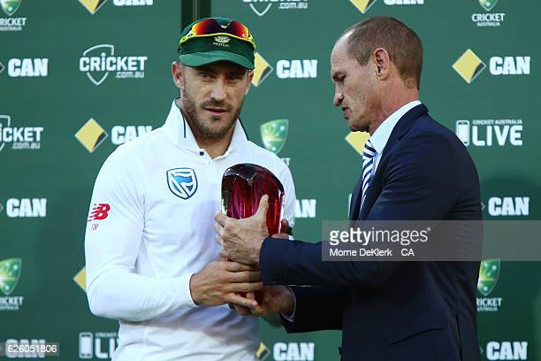 Faf du Plessis of South Africa receives the trophy for winning the series from former cricketer Kepler Wessels after day four of the Third Test match...