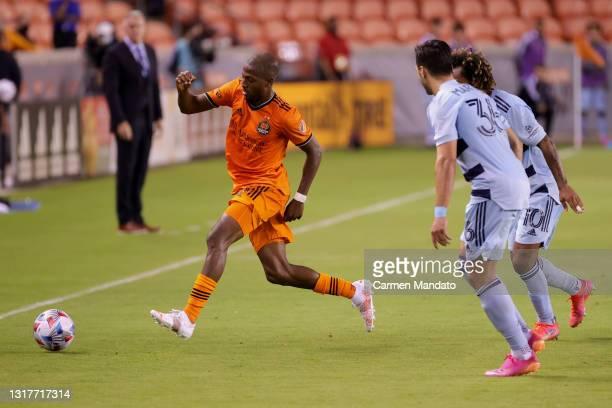 Fafa Picault of Houston Dynamo chases the ball ahead of Luis Martins of Sporting Kansas City at BBVA Stadium on May 12, 2021 in Houston, Texas.