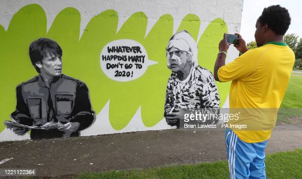 Fahad Aweys stops to photograph Irish artist Emmalene Blake's mural of characters Marty McFly and Doc Brown from the cult 80's movie 'Back to the...