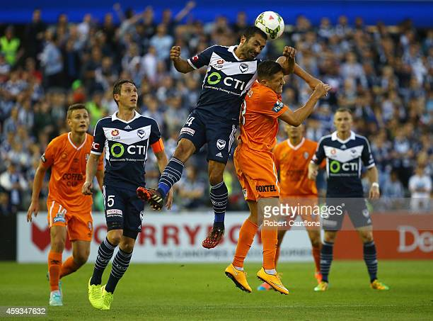 Fahid Ben Khalfallah of the Melbourne Victory heads the ball over Matthew Smith of the Brisbane Roar during the round seven ALeague match between the...