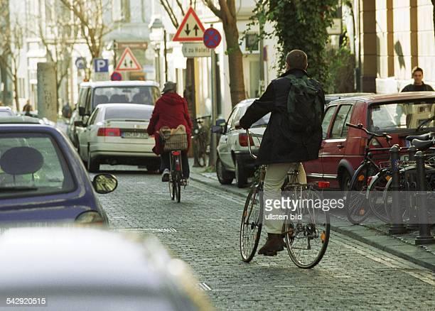 Fahrradfahrer fahren auf der Straße in der Bonner Innenstadt zwischen fahrenden und parkenden Pkws. Verkehrsteilnehmer .
