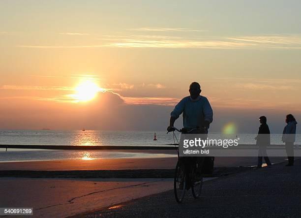 Fahrradfahrer im Abendlicht auf der Promenade der Nordseeinsel Norderney
