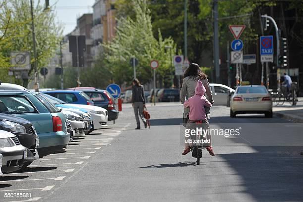 Fahrradfahrerin mit Kind auf dem Gepäckträger in der Knaackstrasse in Berlin-Prenzlauer Berg