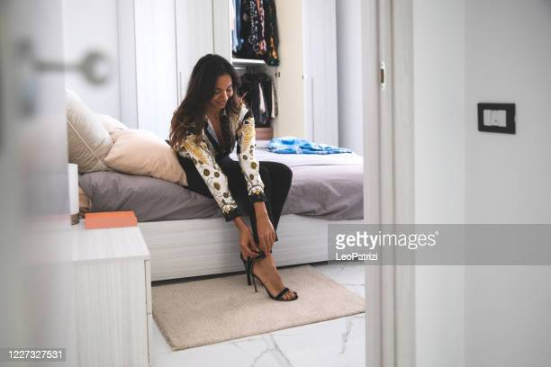 fahsionable woman getting ready to go out to office - women trying on shoes stock pictures, royalty-free photos & images