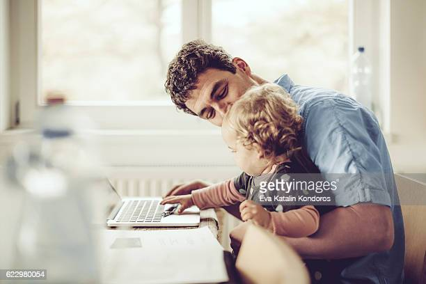 Fahter is showing his daughter things on a laptop