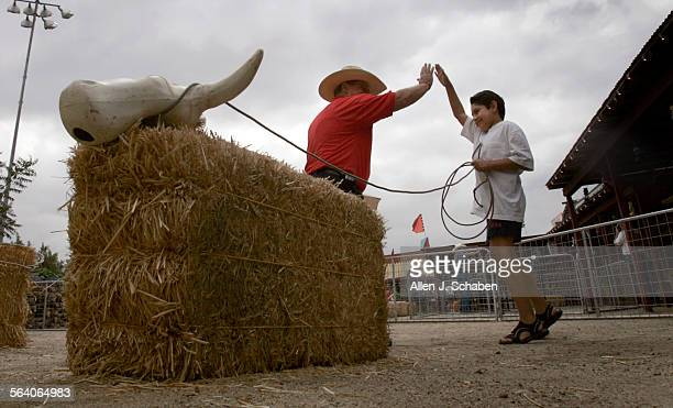 Fair employee Ed Morrison left high–five's Anthony Montero of Long Beach after he successfully performed hand roping on a makeshift calf in the Dude...