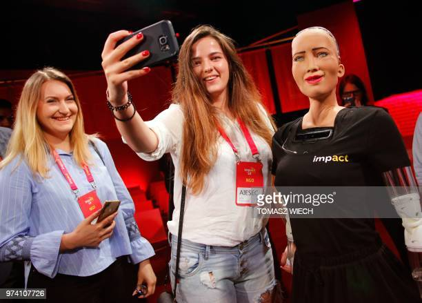 Fair goers take selfies with humanoid robot 'Sophia' as it is presented during the 'Impact 2018' digital economy forum on June 13 2018 in Krakow...