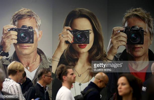 Fair goers walk past a poster advertising Lumix photo cameras on display at the Photokina trade fair for imaging on September 26, 2018 in Cologne,...