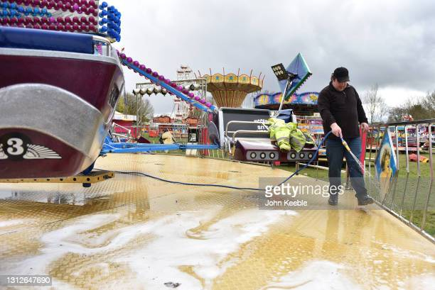 Fair ground worker Tom washes down the Twister ride as Bowdens' fun fair prepares to open tomorrow on April 15, 2021 in Billericay, England. England...