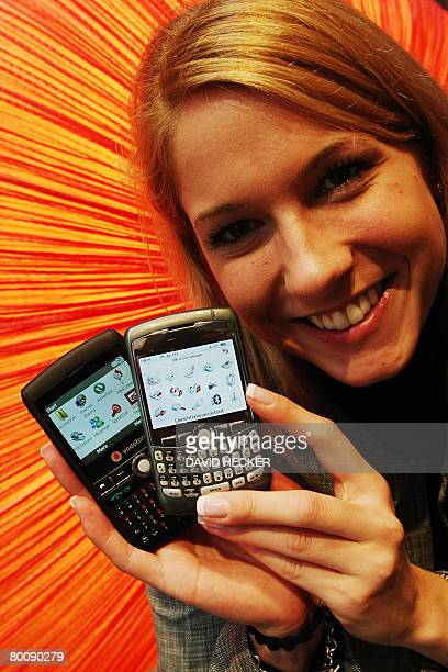 Fair hostess Gabriele stands at the booth of mobile phone provider Vodafone and presents the BlackBerry Pearl 8110 and a Vodafone Blackberry at the...
