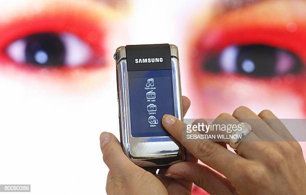 Fair hostess presents a Samsung SGH-G 400 multimedia mobile phone with touchscreen at the CeBIT 2008 trade fair in Hanover on March 3, 2008. The...