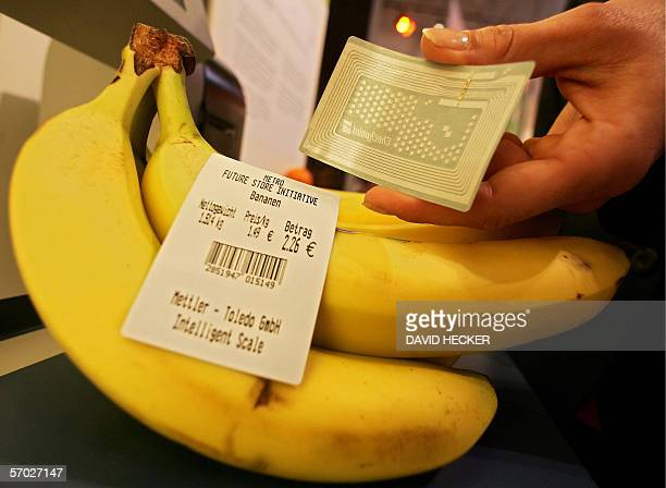A fair hostess presents an RFID label with a microchip besides bananas labelled with a conventional price tag at the stand of the German Metro Group...