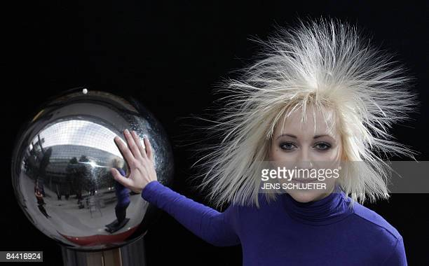 Fair hostess Tanja has her hair electrified as she touches a Van de Graaff generator to promote the enertec International Trade Fair for Energy on...