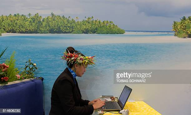A fair hostess uses a laptop at the booth of the Cook Islands at the International Tourism Fair ITB in Berlin on March 10 2016 / AFP / TOBIAS SCHWARZ