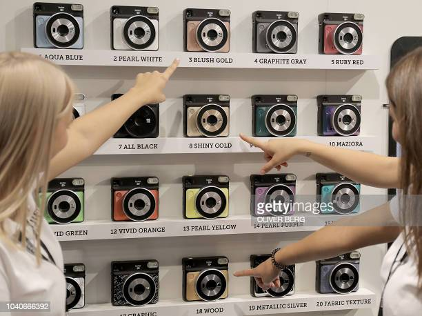 Fair hostesses point on Fujifilm Instax Square SQ6 instand cameras in different colors on display at the Photokina trade fair for imaging on...