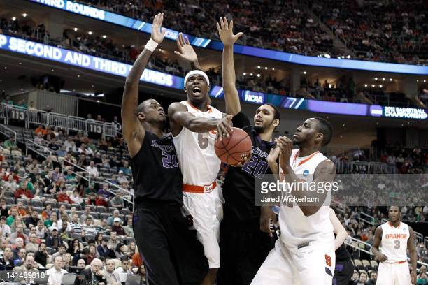 J Fair of the Syracuse Orange drives for a shot attempt in the first half against Jordan Henriquez and Adrian Diaz of the Kansas State Wildcats...