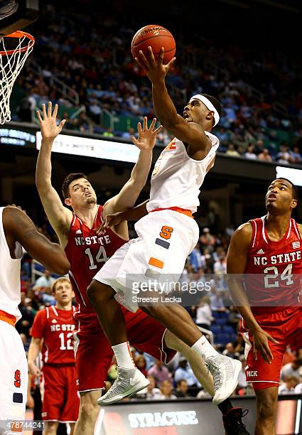 J Fair of the Syracuse Orange drives to the basket against teammates Jordan Vandenberg and TJ Warren of the North Carolina State Wolfpack during the...
