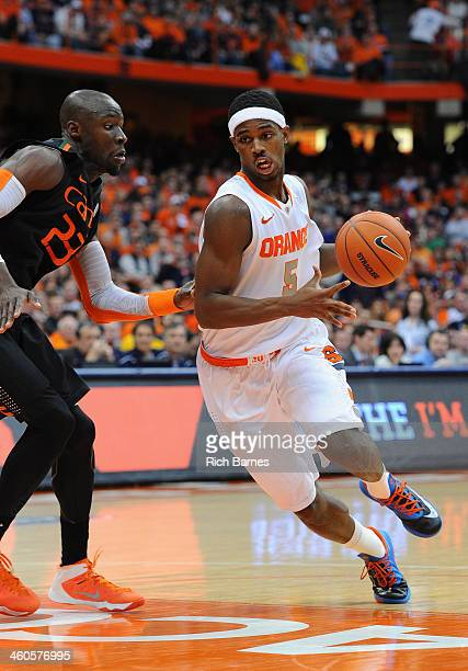 J Fair of the Syracuse Orange drives to the basket around the defense of Tonye Jekiri of the Miami Hurricanes during the second half at the Carrier...