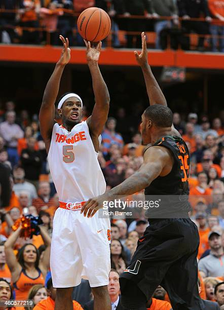 J Fair of the Syracuse Orange takes a shot around James Kelly of the Miami Hurricanes during the second half at the Carrier Dome on January 4 2014 in...