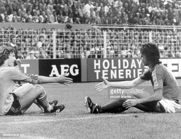 Dutch defender Ruud Krol and Swedish striker Ralf Edstroem are shaking hands after both players fell in a tackle The 1974 FIFA World Cup match at...