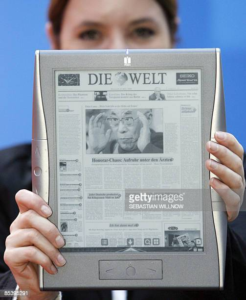A fair worker presents an epaper the newspaper page on an ebook screen at a stand at the Leipzig Book Fair on March 12 2009 at the fair grounds in...