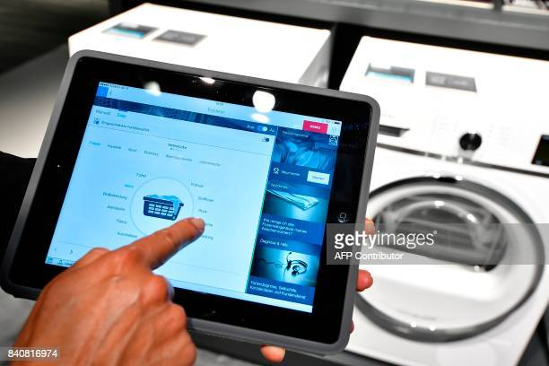A fair worker uses a tablet to operate a tumble dryer during a demonstration how to operate smart controlled household appliances for 'IQ800' washing...