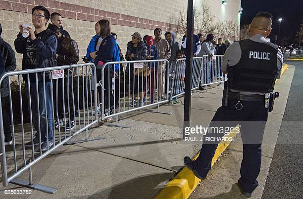A Fairfax County Police Officer keeps an eye on Black Friday shoppers waiting in line in Fairfax Virginia on November 24 to be some of the first...