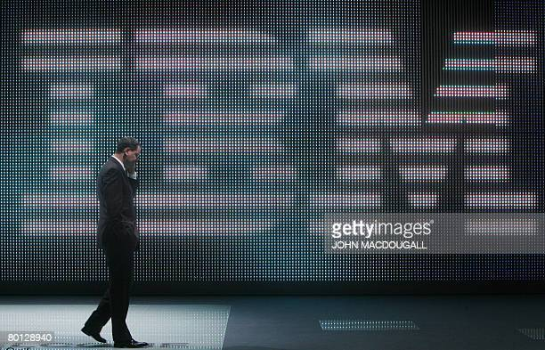 Fairgoer speaks on his mobile phone in front of a giant IBM logo at the CeBIT trade fair in Hanover on March 5, 2008. The fair officially runs from...