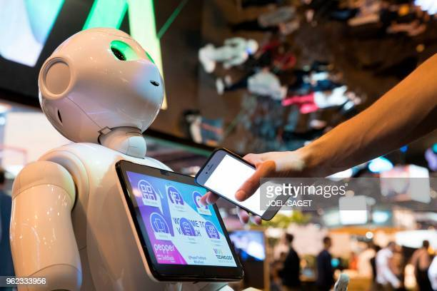 A fairgoer uses a touchpad of Pepper a humanoid robot manufactured by SoftBank Robotics at the SoftBank Robotics exhibition stand during the VivaTech...