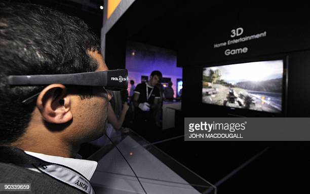A fairgoer wears special '3D' glasses as he watches a video game on a 3D TV screen the stand of Japanese electronics giant Sony at the IFA...